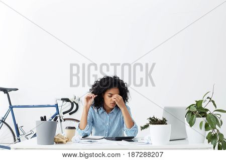 Stressed And Frustrated Young Dark-skinned Businesswoman Feeling Tired And Sleepy While Doing Paperw