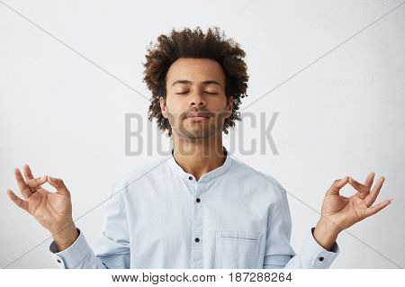 Body Language. Handsome Unshaven Young Dark-skinned Male Yoga Instructor Having Calm And Peaceful Lo