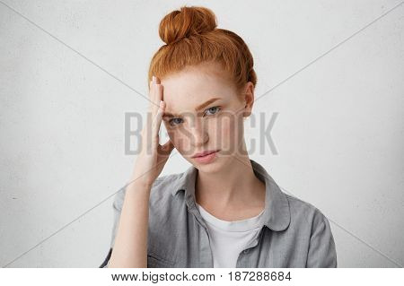Sadness And Sorrow. Sad Girl Wearing Her Ginger Hair In Bun Holding Forehead And Looking At Camera W