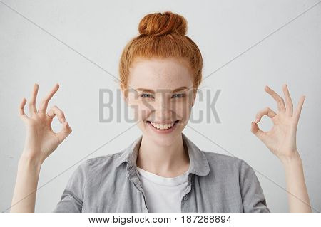 Everything Is Just Fine! Cheerful Excited Young Caucasian Female With Ginger Hair Knot And Freckled