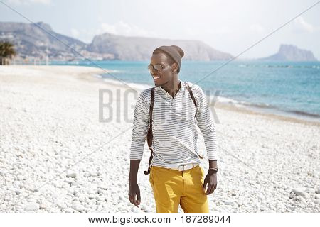 Summer Outdoor Portrait Of Cheerful Black European Student Spending Leisure Time On Beach With Frien