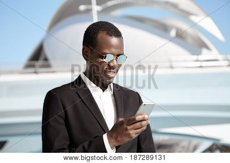 Young Black Man Wearing Black Elegant Suit And Fashionable Round Sunglasses Standing Against Citysca