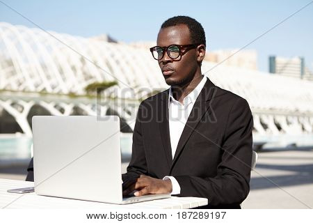 Outdoor Portrait Of Successful Office Worker In Eyewear And Black Suit Sitting At White Desk Surroun