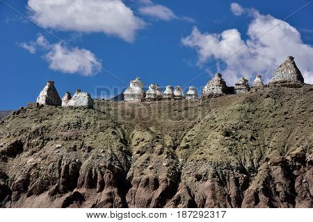 White Buddhist Tibetan Ancient Stupa On The Crest Of High Mountain Under A Blue Sky With Clouds, Tib