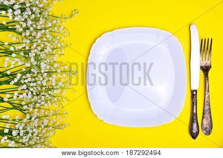 White plate and iron vintage cutlery on a yellow background and a bouquet of white lilies of the valley top view