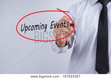 Businessman Hand Writing Upcoming Events with a marker over transparent board Events concept.