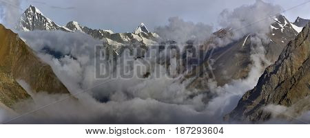 Huge high mountains the valley is shrouded in the morning mist: solid gray clouds lie along the valley peaks with snow rise above the clouds the sun Tibet.