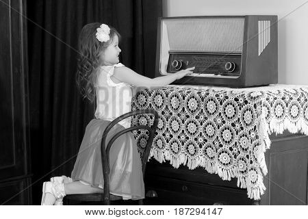 Beautiful little girl with interest looking at an old tube radio. This receiver she sees for the first time.Black-and-white photo. Retro style.