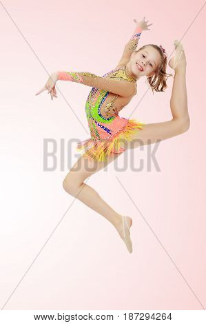Beautiful little girl gymnast dressed in sports swimsuit for competitions, performs a jump.Pale pink gradient background.