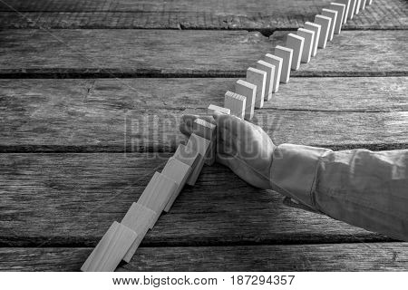 Monochrome Image Of A Businessman Preventing Dominoes From Crumbling