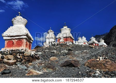 Many ancient Buddhist stupa on the steep of the mountain under a bright blue sky: the stupas are set on a stony hill below are red patterns the valley of Nubra Northern India.