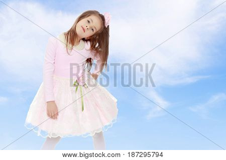 Dressy little girl long blonde hair, beautiful pink dress and a rose in her hair.She put forth a foot.On the background of summer blue sky and fluffy clouds.