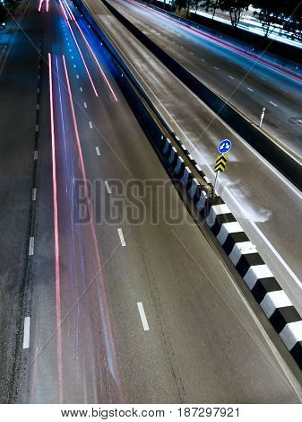 Lane Splitter on a Highway with a Sign in the Evening