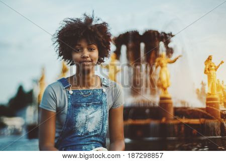 Tilt-shift portrait of young cute afro american girl in jeans overalls sitting in front of beautiful fountain