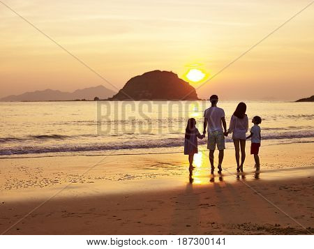 asian family standing on beach watching and enjoying the sunrise or sunset.
