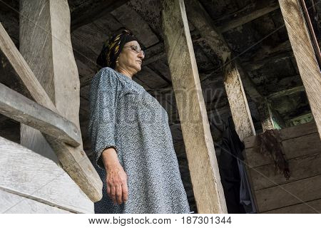 Portrait of a Muslim woman standing in wooden hut portico.