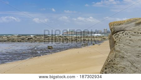 Australian beach panorama with sandy foreground rocks reef crashing waves ocean horizon and blue sky
