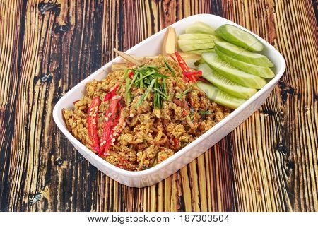 Thai southern traditional styleSpicy roasted mince chicken with yellow curry pastecall Khua Kling in Thaitopped sliced chilicucumber and correspondentsfried hot southern chilli paste with chicken