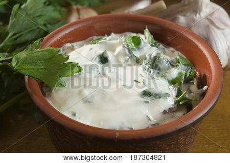 Garlic dip sauce with fresh green parsley leaves