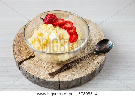 close up of corn porridge with strawberries - breakfast served on natural sawed wood with vintage spoon