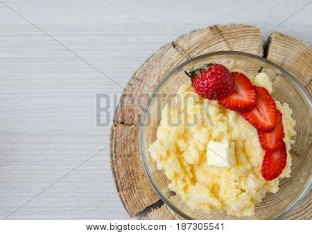 corn porridge with strawberries - breakfast served on natural sawed wood top view. space for text