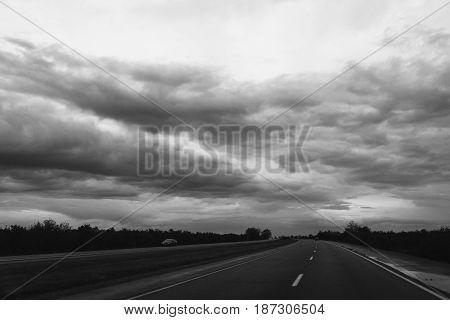 Dark storm clouds over highway landscape in Colorado, USA.