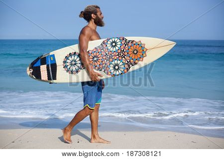 Full-length portrait of an attractive bearded curly man with a surfboard is walking on a beach going from the left side to the right side of the frame