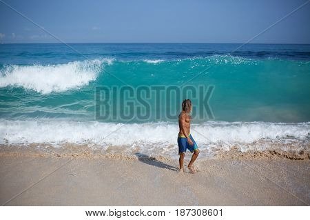 Attractive muscular curly blond wet man with naked fit torso is going out of the sea and looking at the big wave rising behind him