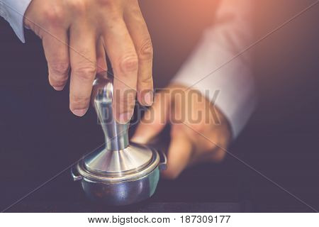 Hand Of Barista Using Tamper To Press Ground Coffee Into Portafilter In Cafe For Prepare To Make Esp