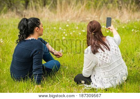 Two friends women making photos in nature with smartphone