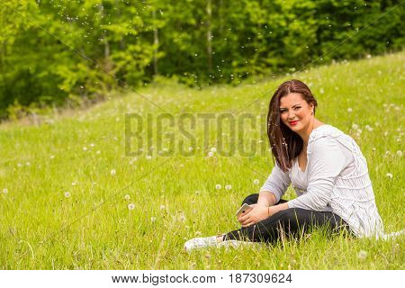Woman with dandelions seeds around her in nature