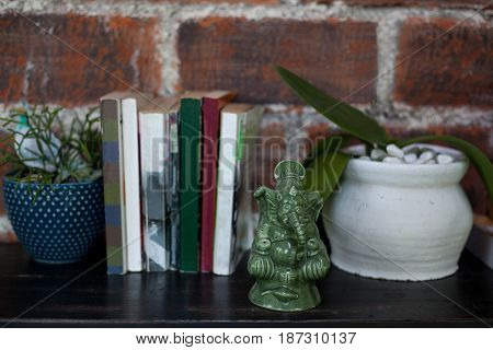 Home interior decor a ceramic statuette of Ganesh and flower pots with plants on black wooden commode on red brick wall background