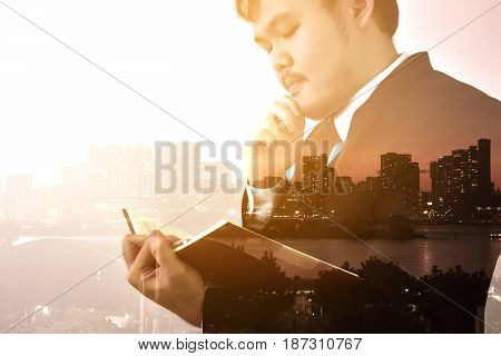 Businessman looking memo and Thinking for idea,Double exposure, panoramic view contemporary megalopolis background, orange sun light