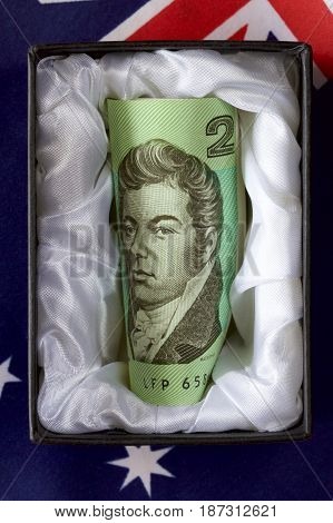 Discontinued Australian two dollar note in a coffin with a flag.