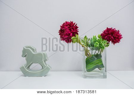 Beautiful Dahlia Flowers And Seramic Horse In Grass On Light Background