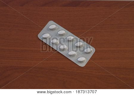 Pills packed in blisters. Tablets on a wood background.