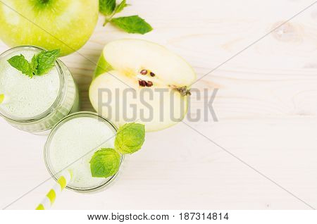 Freshly blended green apple fruit smoothie in glass jars with straw mint leafs cut apples top view. White wooden board background copy space.