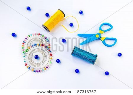 Sewing spools of blue and yellow caprone threads, plastic scissors, glass beds and colorful pins on white background