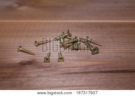 Self-tapping screws on a wooden background. Close-up.