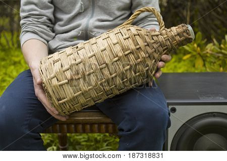 Man sitting on a chair with a wicker bottle in hands next to a loudspeaker. Outdoor cropped shot