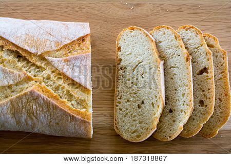 Slices and loaf of bread on wooden oak table top. Shallow depth of field.