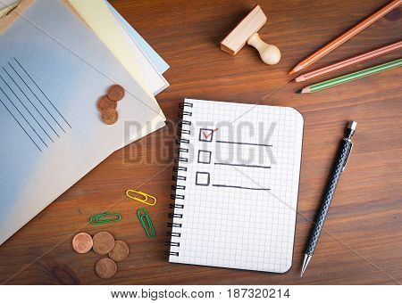 Book with blank checklist on wooden table.