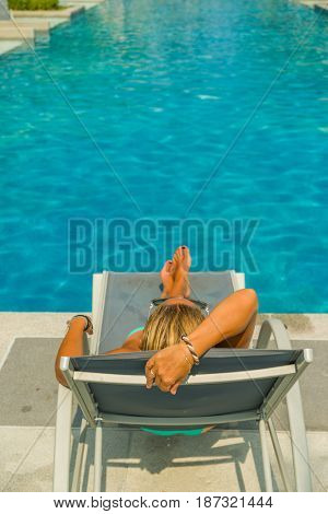 Woman at the swimming pool relaxing on a sun lounger