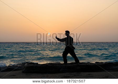 Man performs tai chi moves silhouetted agains sunset