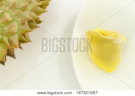 Durian on a white plate with green spikes rind and white background king of the fruit but smelly in Thailand and south east asia; soft focus