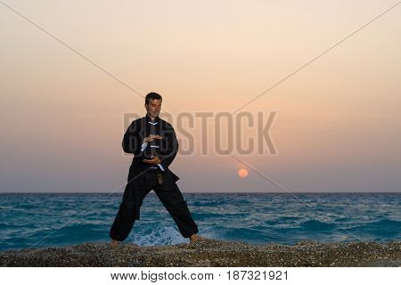 man performs tai chi moves silhouetted agains sunset at the beach