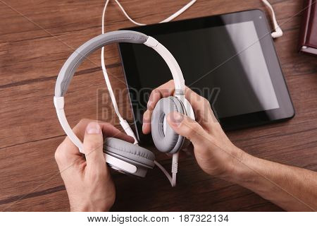 Audio book concept. Young man using tablet and headphones, close up