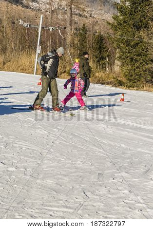 Dad With Daughter On The Ski Slope.