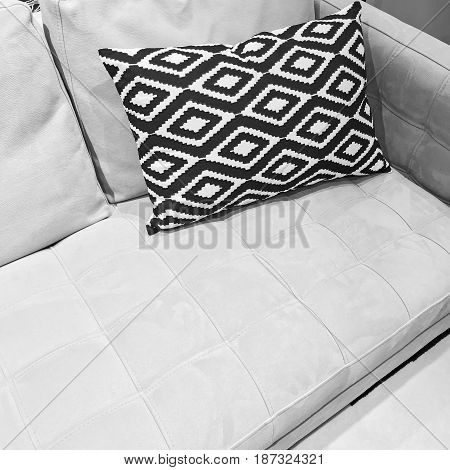Black and white ornamental cushion on a gray sofa. Stylish modern furniture.
