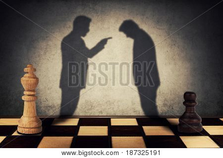 Chess pawn and king standing in front one another with their shadow transform into businessman silhouettes. Business hierarchy misunderstanding concept.
